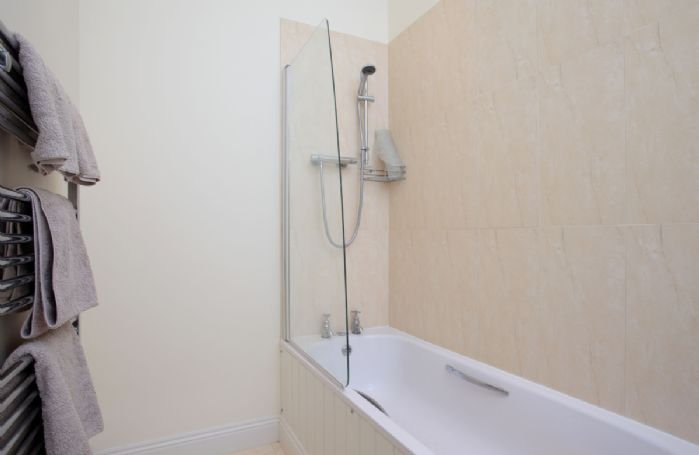 Upper ground floor: En-suite bathroom with bath and shower over
