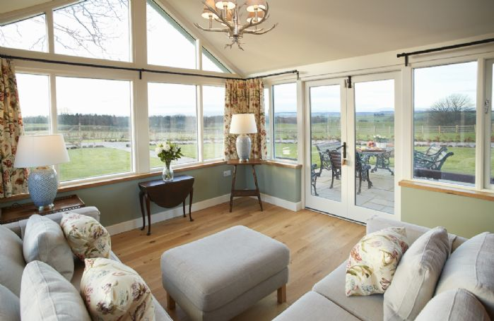 Ground floor: Day room with seating and access through french doors to a sandstone patio