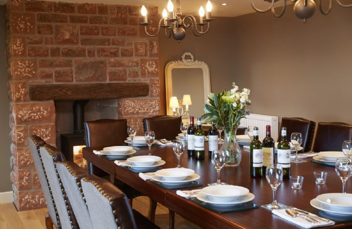 Ground floor: Dining room with table seating twelve guests and wood burner