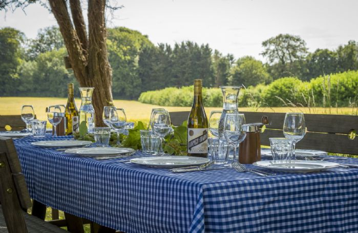 Orchard garden with shaded garden table seating ten guests and beautiful views