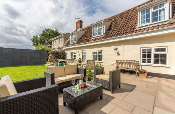 Private patio area with bi-fold doors leading into the stunning cottage