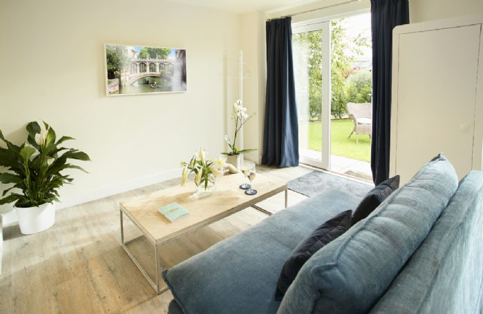 Ground floor: Open plan living area with comfortable sofa and french doors leading out to the garden