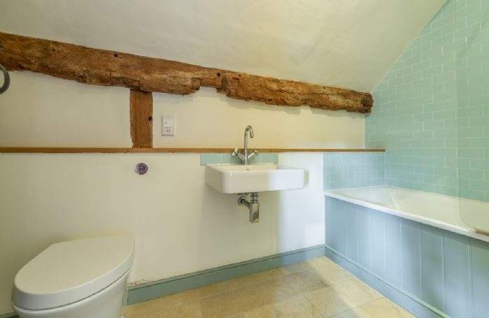 Butley Barn first floor: Bedroom four en-suite with shower over the bath