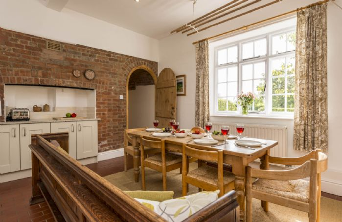 Ground floor: Fully equipped farmhouse kitchen with dining table and door leading to the sitting room