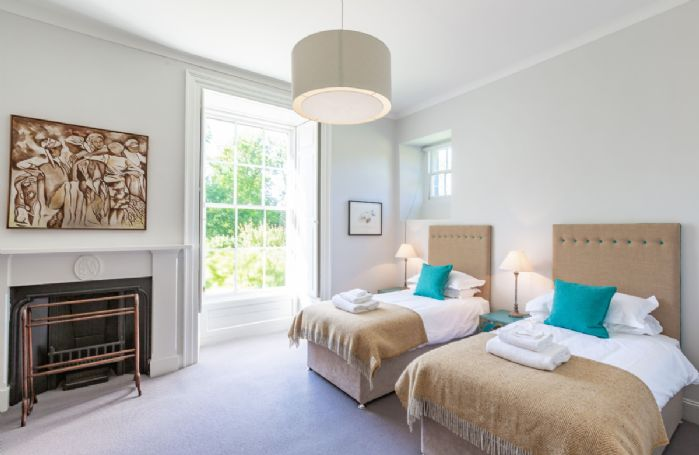 First floor: Bedroom two with 6' super king size zip and link bed and feature fireplace