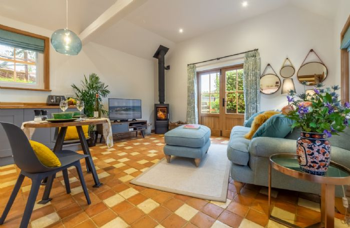 Ground floor: Open-plan sitting room with woodburning stove and french doors leading to the garden