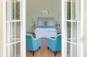 Lower Ground floor:  Double bedroom with a king-size bed, armchairs and french doors leading to a private patio