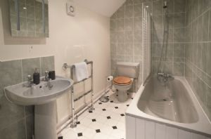 First floor: En-suite bathroom with bath and overhead shower