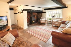Ground floor: Sitting room with inglenook fireplace, wood burning stove and original flagstone floor