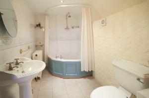 First floor: En-suite bathroom with corner bath and overhead shower