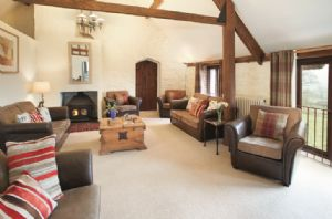 First floor: Large sitting room with wood burning stove, exposed beams and spectacular south facing views