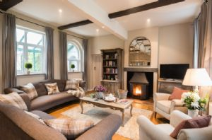 Ground floor: Sitting room with wood burning stove and patio door to back patio and garden
