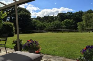 Back garden and patio with rattan sofas and badminton net