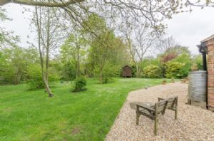 South-facing gravelled patio with garden furniture, plus access to wooded grassed enclosed garden
