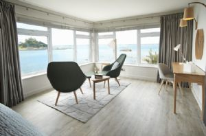 The master bedroom interior design is stylish and fresh with light oak furniture and an accent of warm coastal tones relax and admire the view across to St Michael's Mount from the master bedroom
