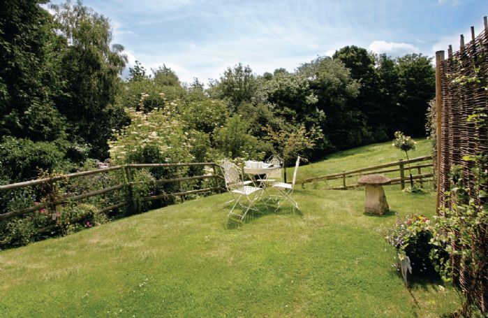 Small private lawned garden with garden furniture