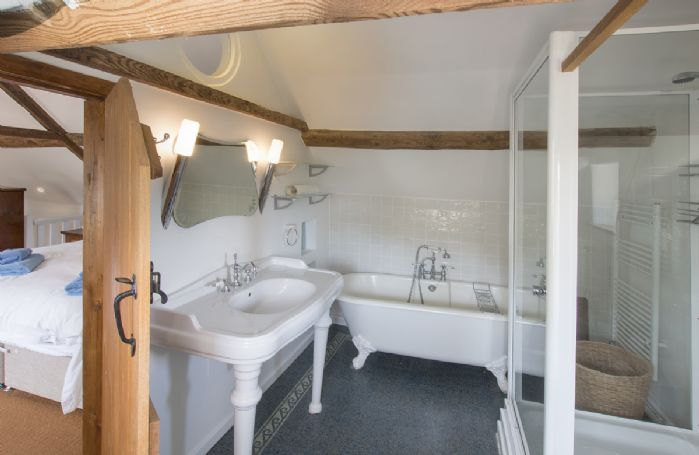 First floor: Large en-suite bathroom with roll top bath and walk-in shower