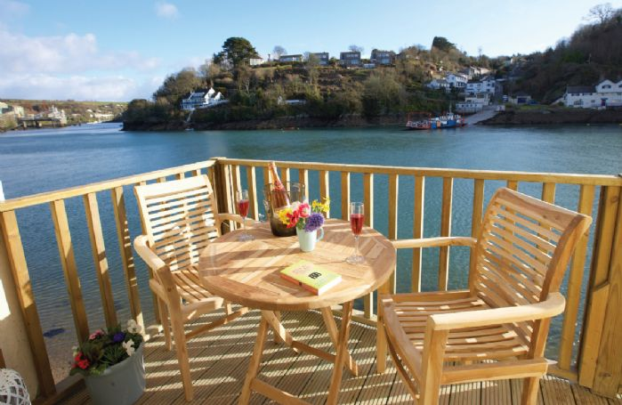 Decked balcony area with outdoor table and chairs, mooring and steps down to the water