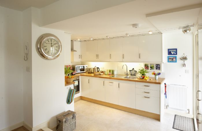 Open plan kitchen/sitting/dining room with double glass doors leading to the decking