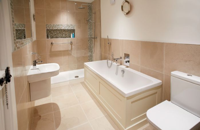 Ground floor: En-suite bathroom with bath and separate rainfall shower