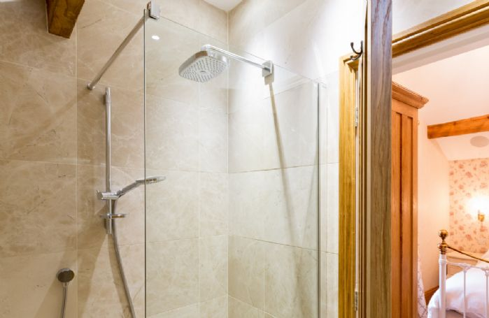 First floor: Hallin - en-suite natural stone shower room with monsoon and raindrop showers and views across Hallin Fell