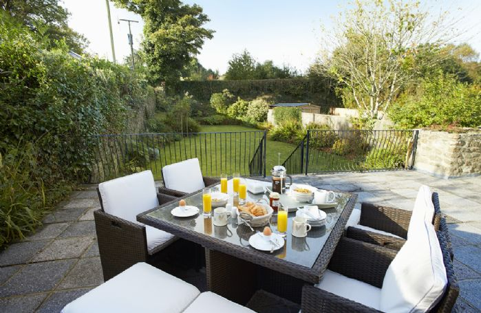 Fully enclosed rear garden with garden furniture and barbecue