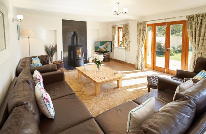 Ground floor: Large sitting room with wood-burning stove and French doors leading out to the large level garden