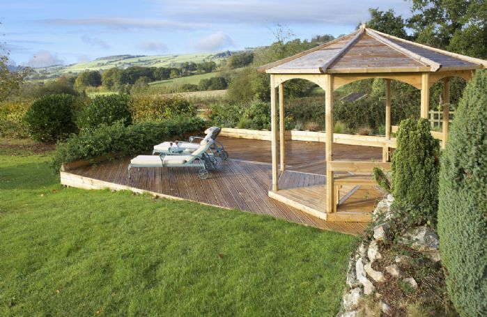 Decking with gazebo and patio with garden furniture
