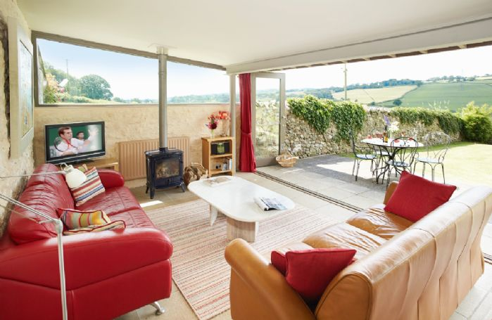 Ground floor:  Sitting room with wood burning stove and large glazed doors opening onto the terrace with stunning views