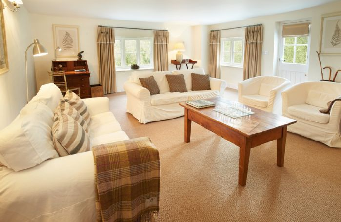 Ground floor: Spacious sitting room with electric wood burner and comfortable sofas
