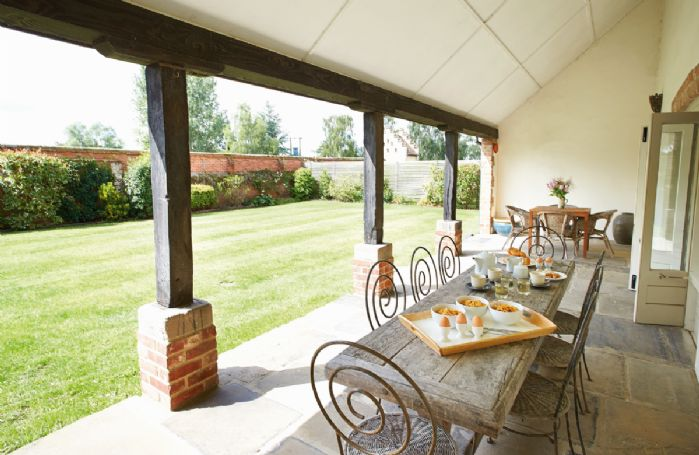 Covered loggia - for al fresco dining - which overlooks the private south-facing walled garden with views to the Hall