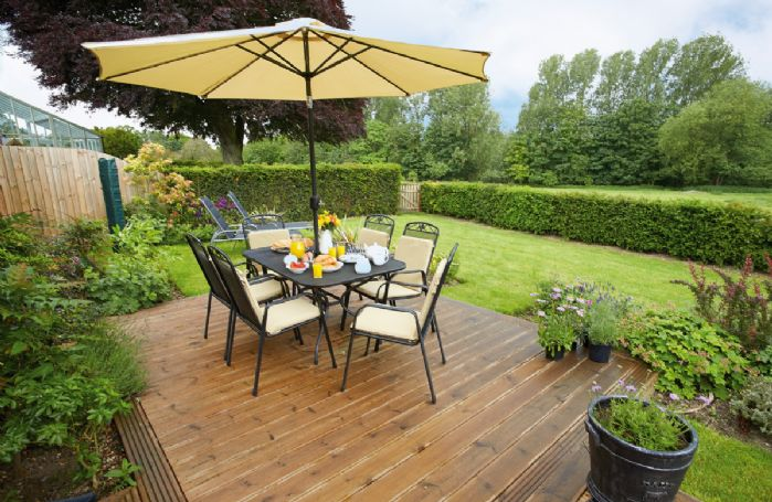 Enclosed rear garden with garden furniture and barbecue