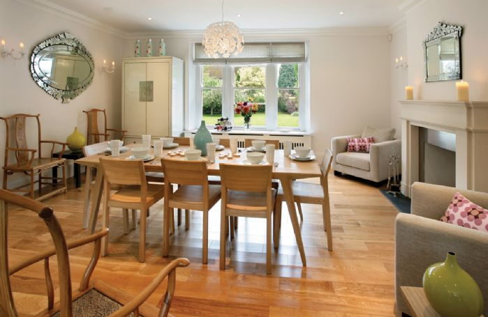 Ground floor: Dining room with open fire and armchairs which opens onto kitchen
