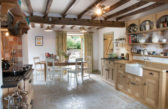 Ground floor:  Large, well equipped farmhouse dining kitchen with beamed ceiling, French doors opening onto ornamental garden and patio with bistro style furniture