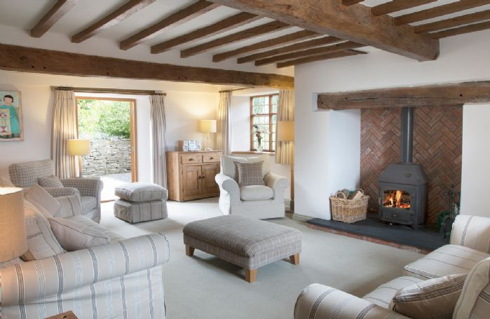 Ground floor:  Spacious beamed sitting room with inglenook fireplace and wood burning stove with French doors to rear garden