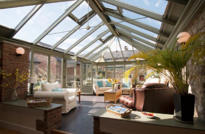 Conservatory with southerly aspect opening into a private courtyard with garden furniture