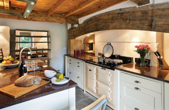 Ground floor:  Kitchen/breakfast room featuring a beamed fireplace with Aga