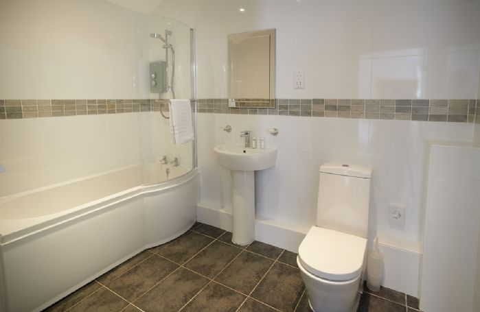 Ground floor: En-suite bathroom with low sided bath with shower over