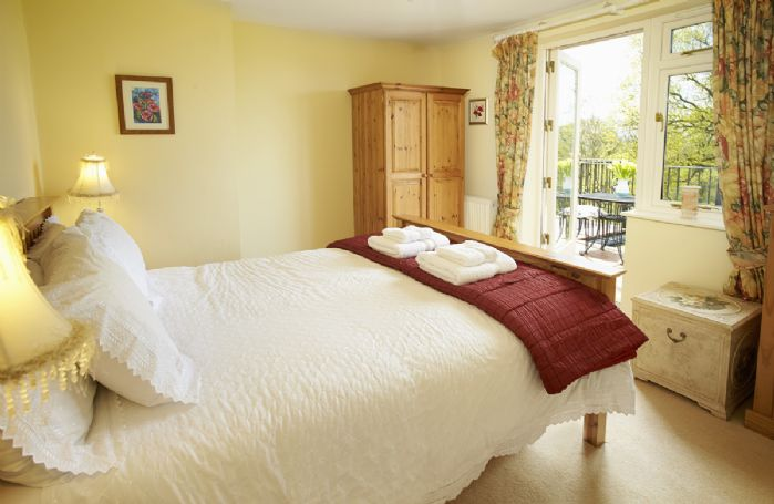 First floor: Double bedroom with 5' bed and patio doors leading onto the balcony