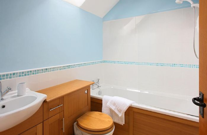 Orchard Cottage:  First floor: Fully tiled bathroom with fitted shower, wc and sink