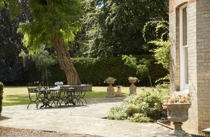 Large Yorkstone terrace at front overlooking lawns, with lovely stone planters, stylish Oxleys cast iron garden table and chairs and original Victorian Coalbrookedale garden benches