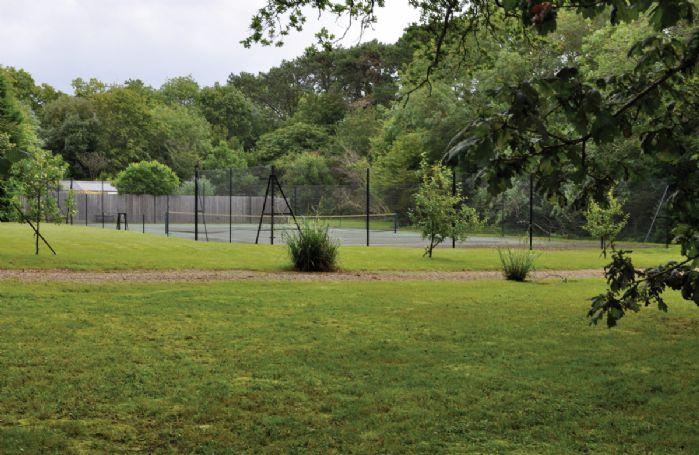 The extensive grounds also include an asphalt tennis court