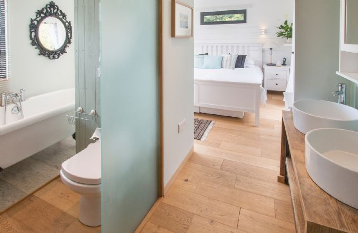 Ground floor:  En-suite bathroom with roll top bath and separate shower - there is a partition, rather than a door between the bedroom and bathroom areas