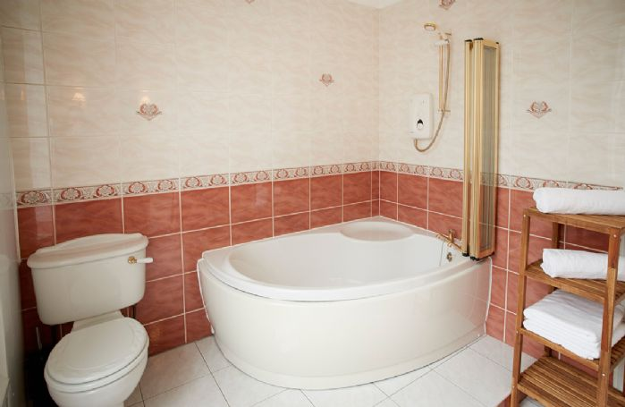 First floor: Bathroom with corner bath and overhead shower