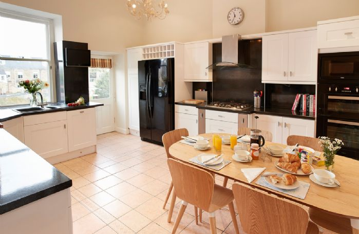 First floor: Spacious kitchen with dining table and chairs