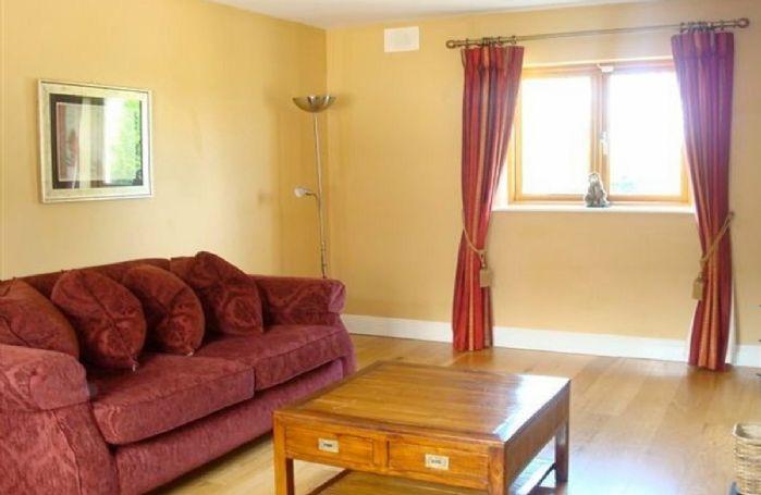 Ground floor:  Sitting room with oak floors and multi-fuel stove
