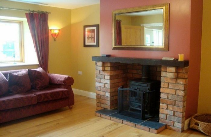 Ground floor: Spacious living room with oak floors and multi-fuel stove