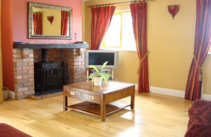 Ground floor:  Spacious sitting room with multi-fuel stove