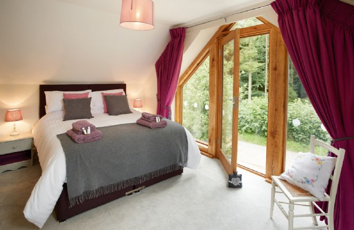 First floor: Bedroom with oak and glass frame windows with views to the woodland, 5' King size bed (bed can be changed to twin upon advance request) with en-suite shower room