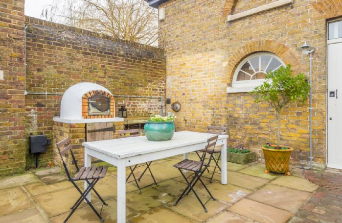 The patio at the back of the house is perfect for outdoor dining and even features a pizza oven